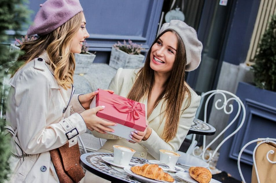 Blonde and brunette women in berets giving gifts in Paris
