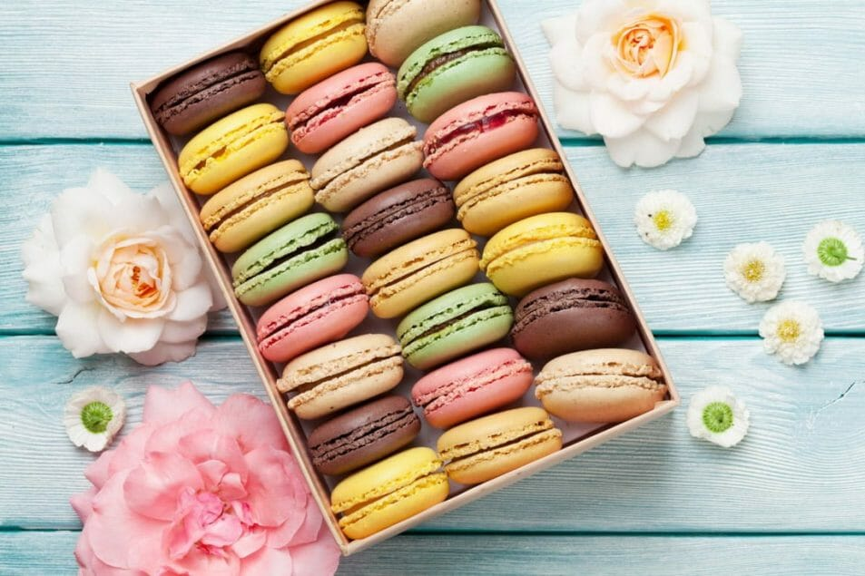 Colorful macarons in a box with flowers