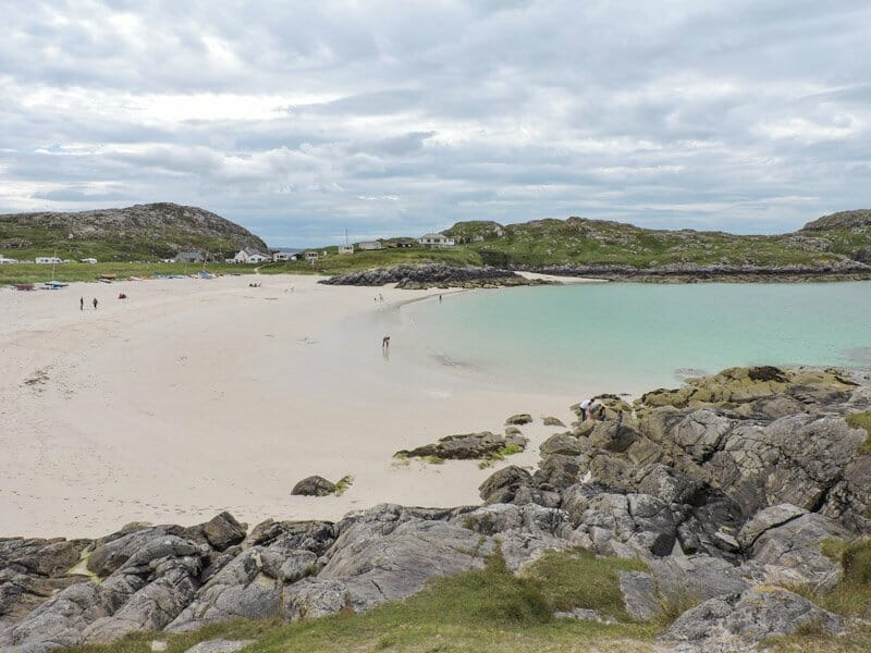 Achmelvich beach, blue sea, white sand, rocks, people North Coast 500 Scotland