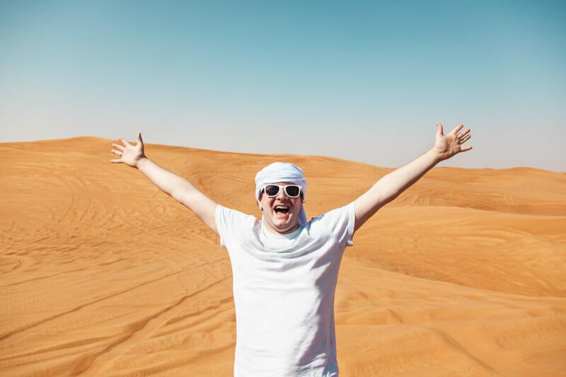 Happy man in Dubai desert wearing head scarf