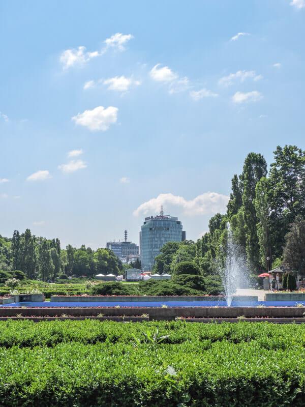 HerastrauPark area of Bucharest, green bush, blue skies, water fountain