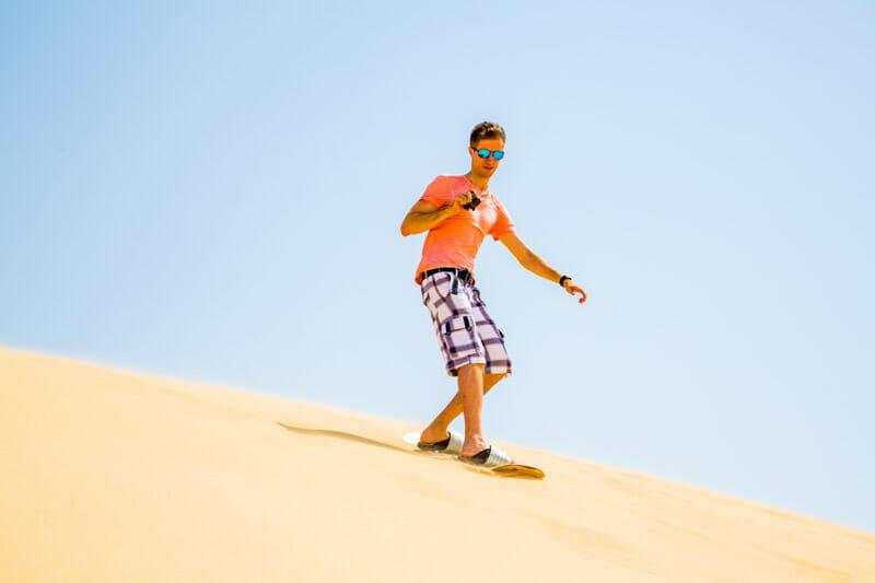 Man sandboarding in desert