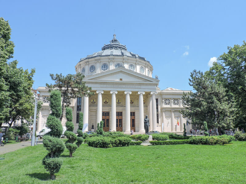 Romanian Athenaeum in Bucharest with green grass and blue skies