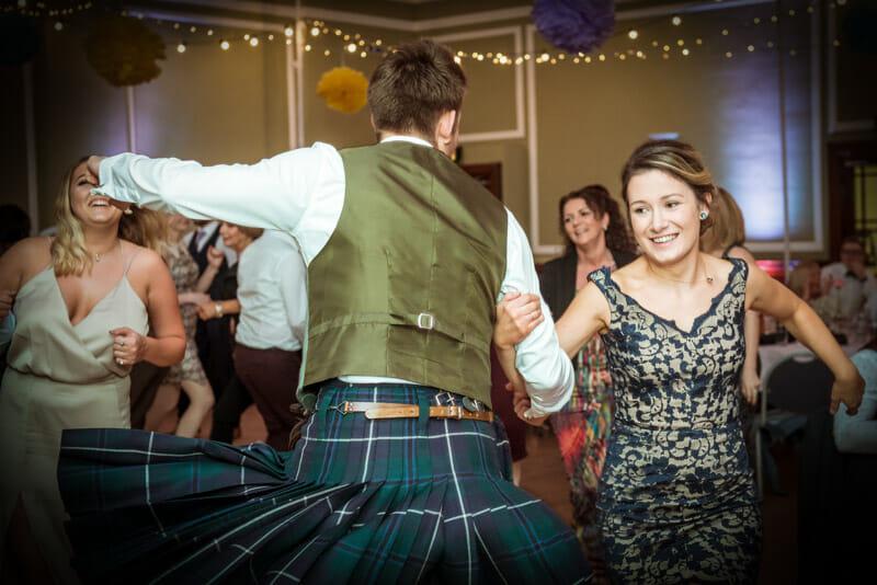 Scottish couple doing ceilidh dance man in a kilt