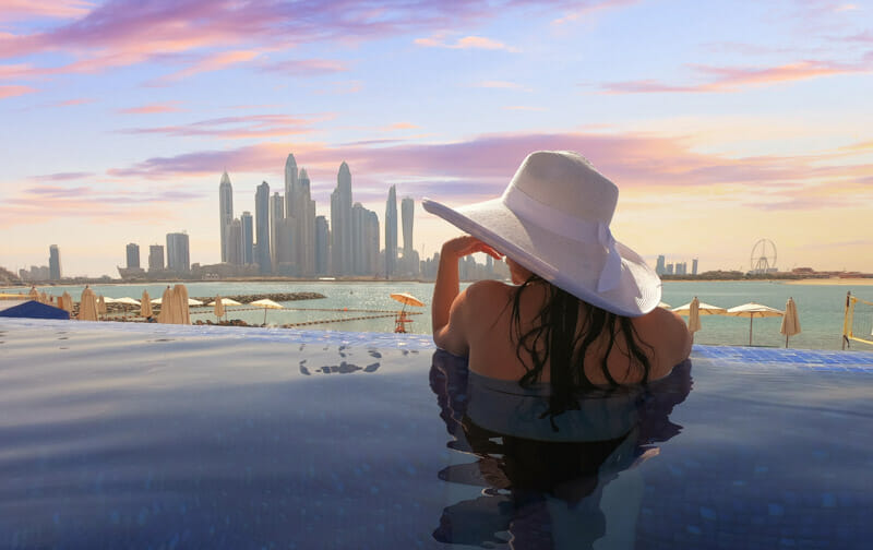 Dubai Skyline Woman With Hat in Pool