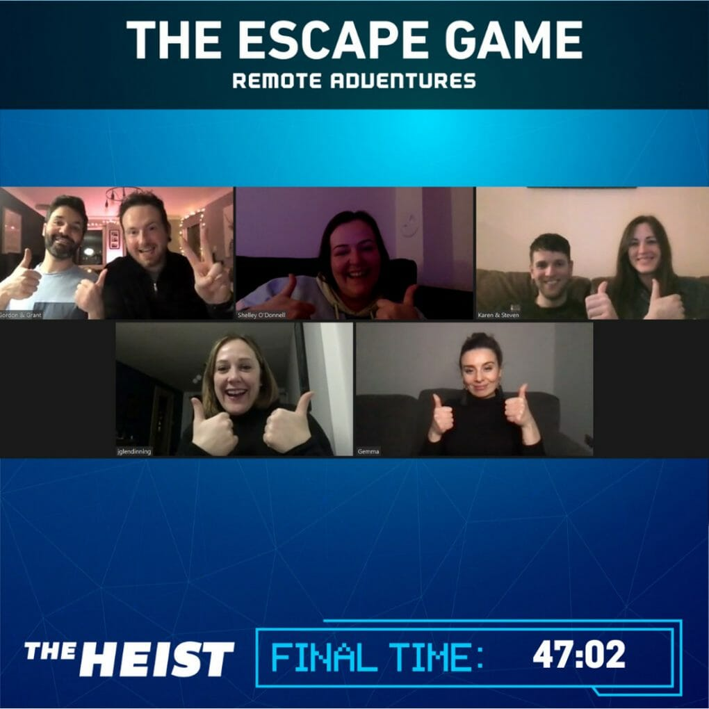 Remote Adventures Virtual Escape Game Group Image. A group of players smile at the Zoom screen with The Heist written underneath the image.