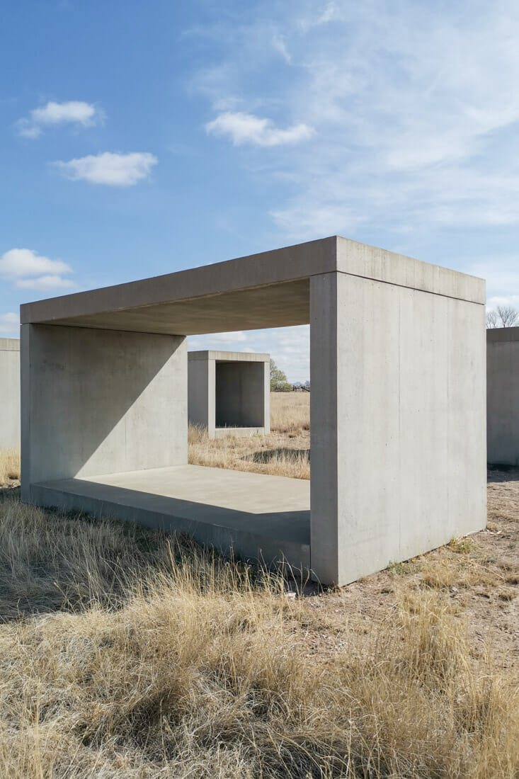 15 Untitled Works in Concrete in Marfa Texas - Two grey concrete hollow boxes on sandy ground with blue skies and shadows