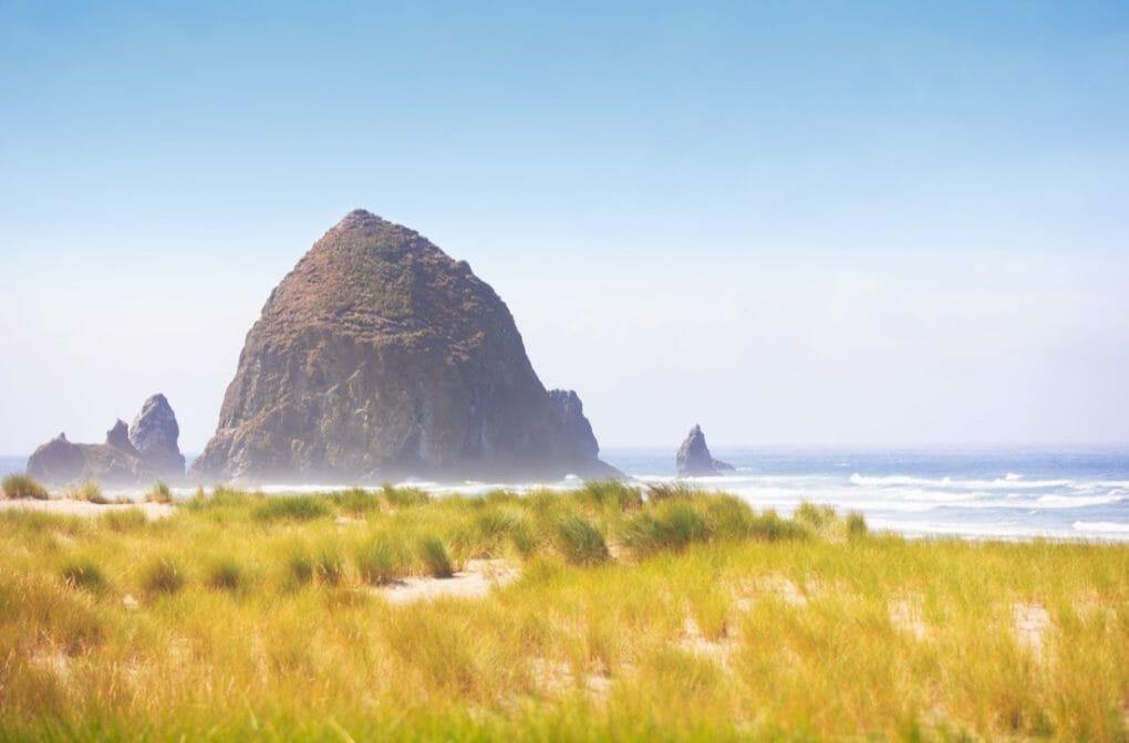 Cannon Beach Oregon landscape of Haystack Rock and grassy beach.