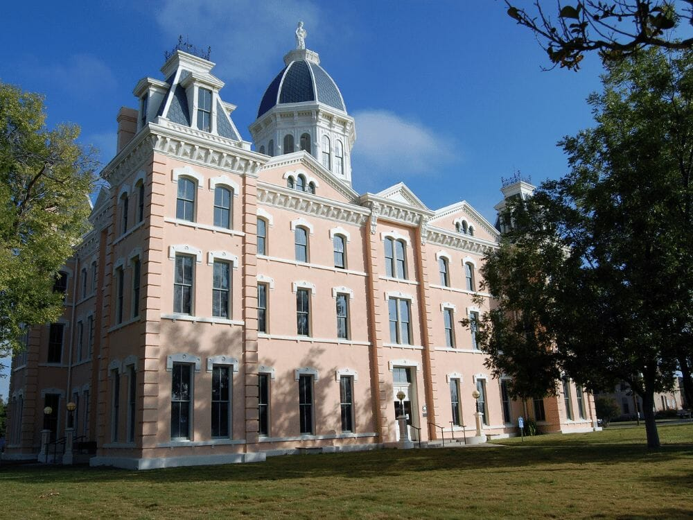Presidio County Courthouse Marfa Texas pink building with blue skies and green grass