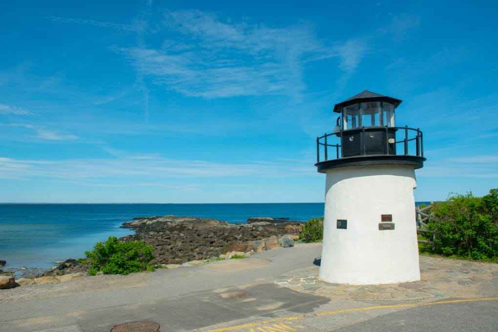 Lobster Point Lighthouse Maine Beach with blue skies